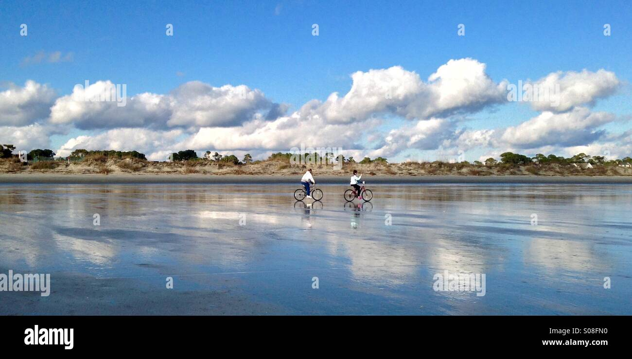 Bicyclists cruise along the sand at low tide on the beach at Kiawah Island, SC. - Stock Image