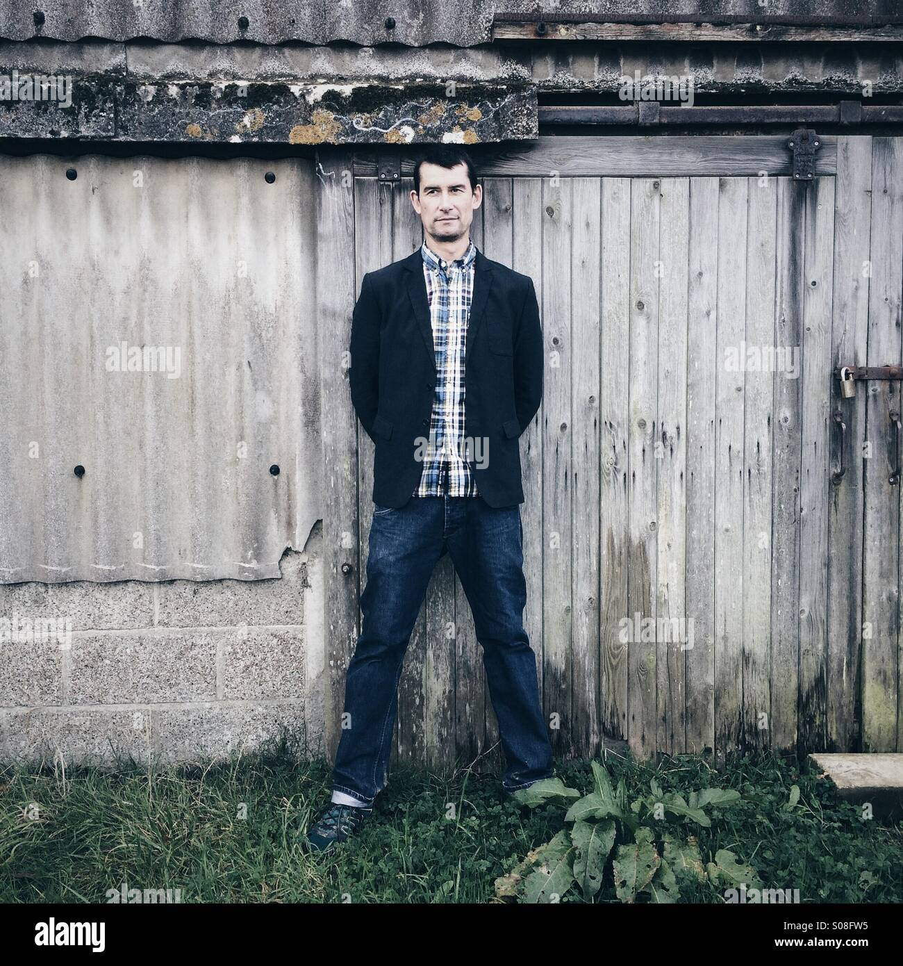 Man standing against a barn, dressed casually in jeans and a jacket. - Stock Image