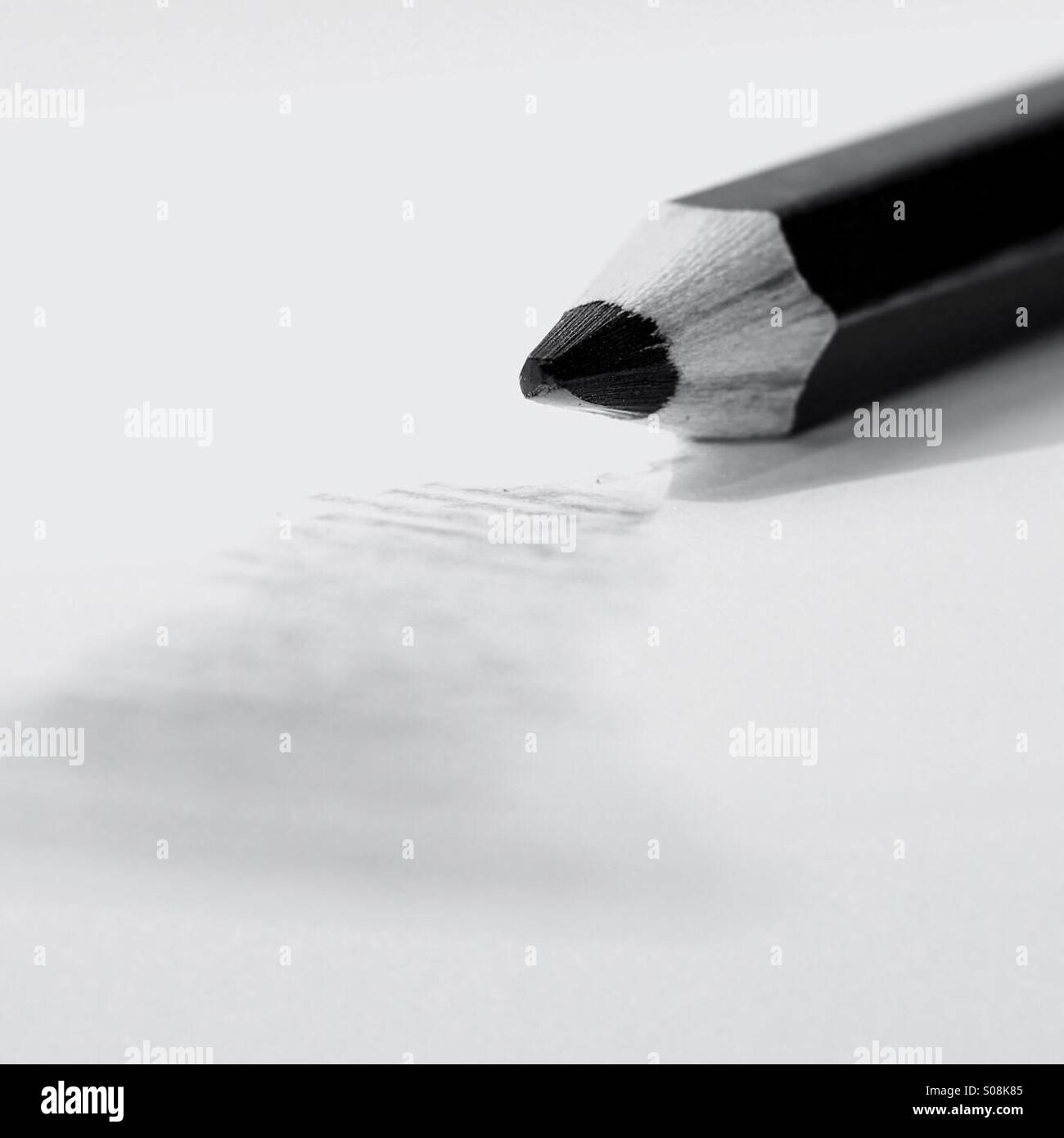 Drawing pencil lies on paper next to scribble - Stock Image