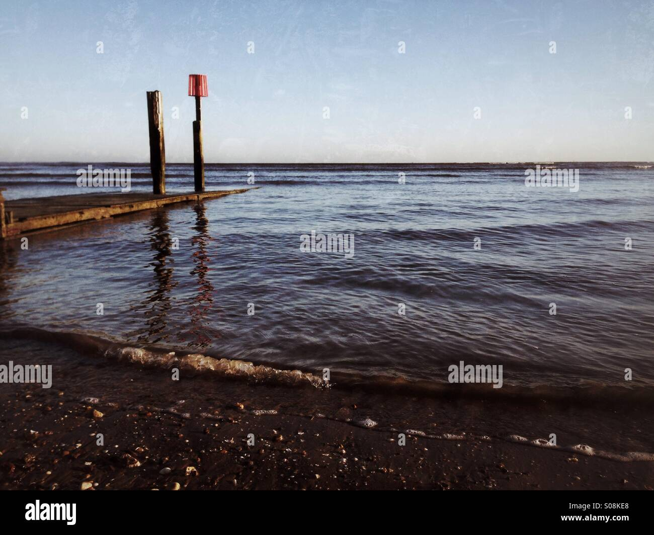 Wooden pontoon and incoming tide. - Stock Image