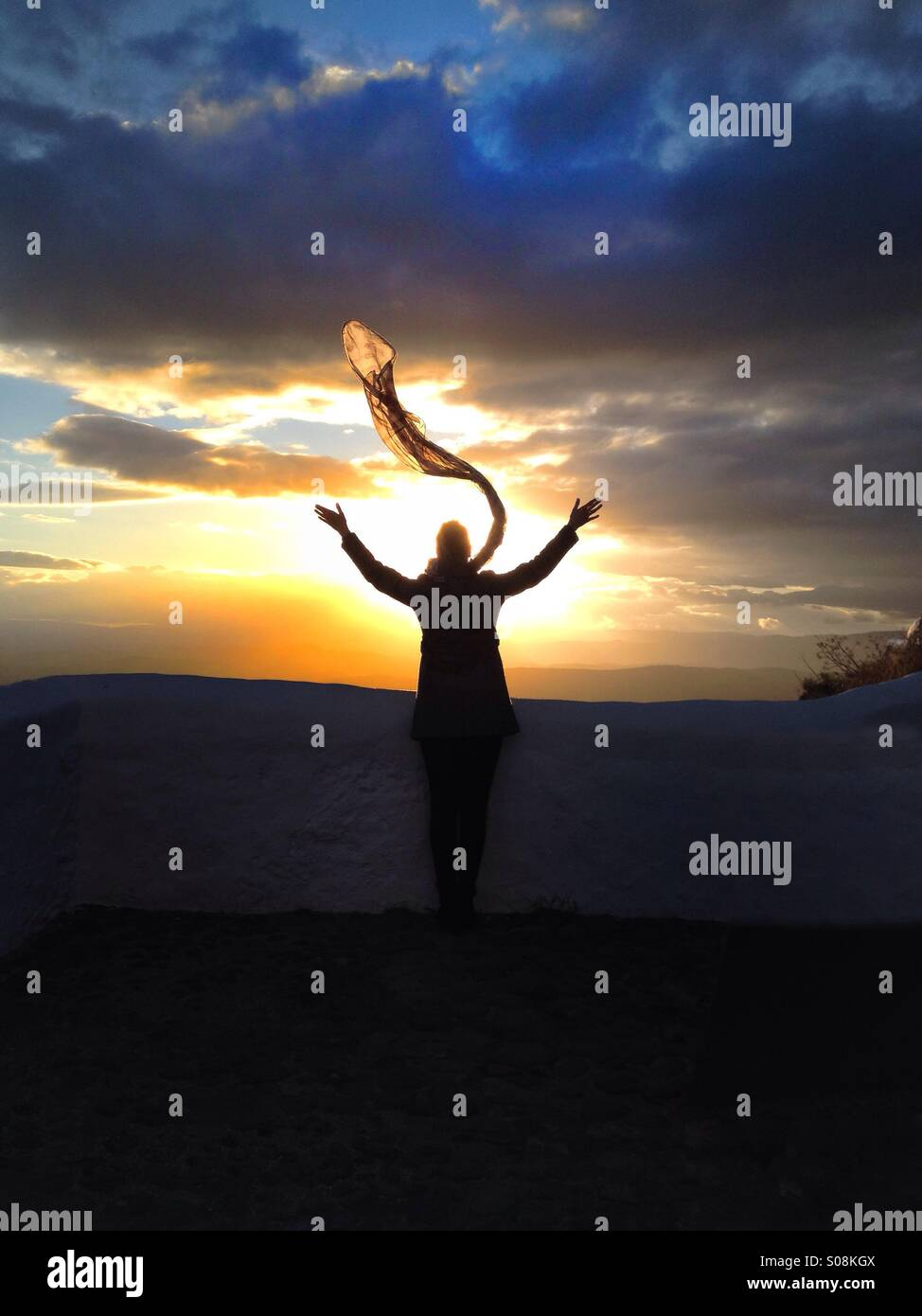Woman with scarf watching sunset - Stock Image