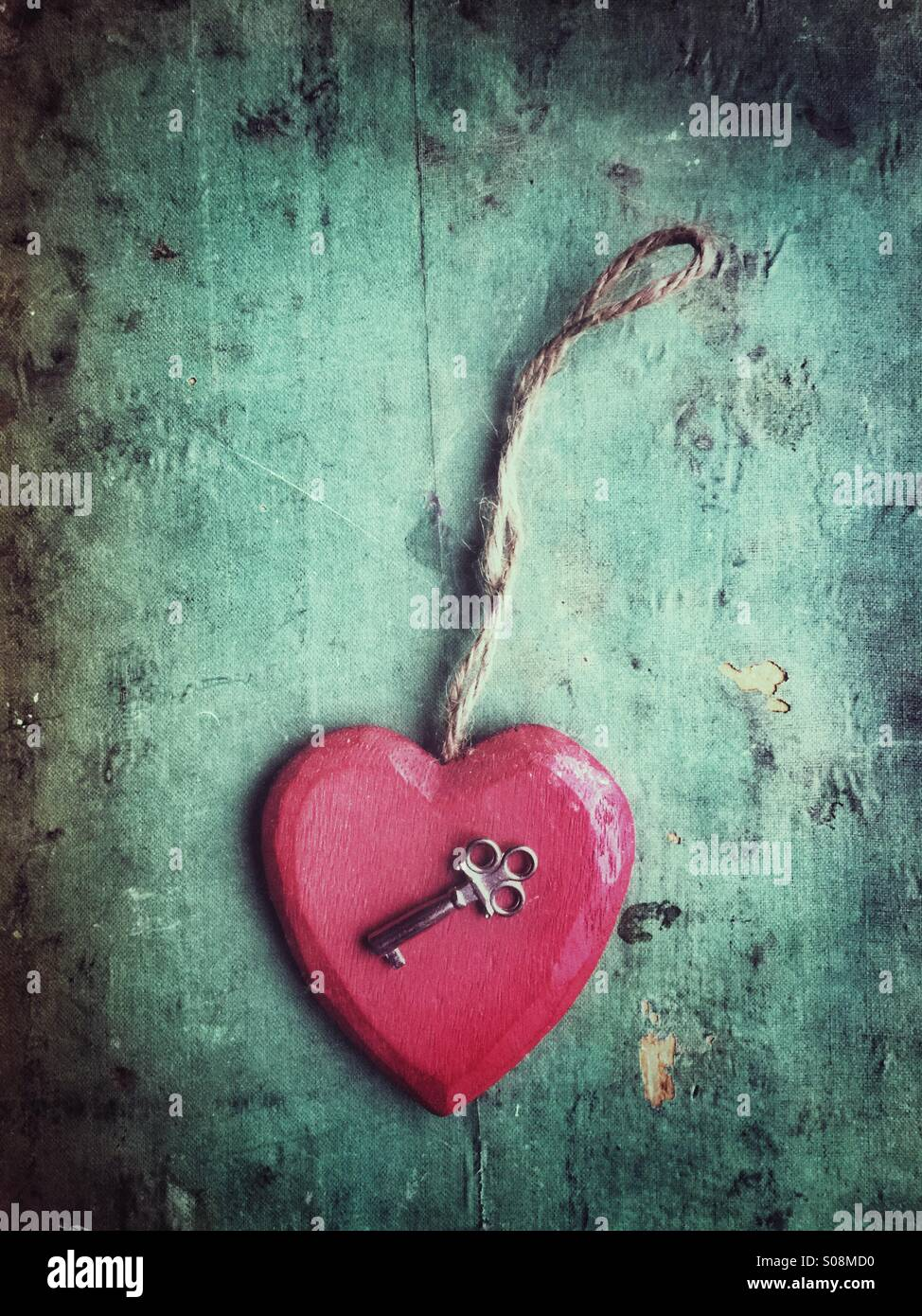 Red wooden heart and a key - Stock Image