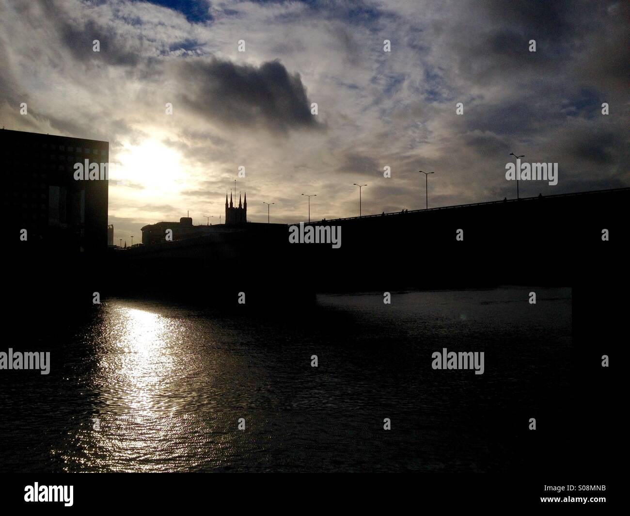Low sun shines on the Thames, London Bridge silhouette - Stock Image