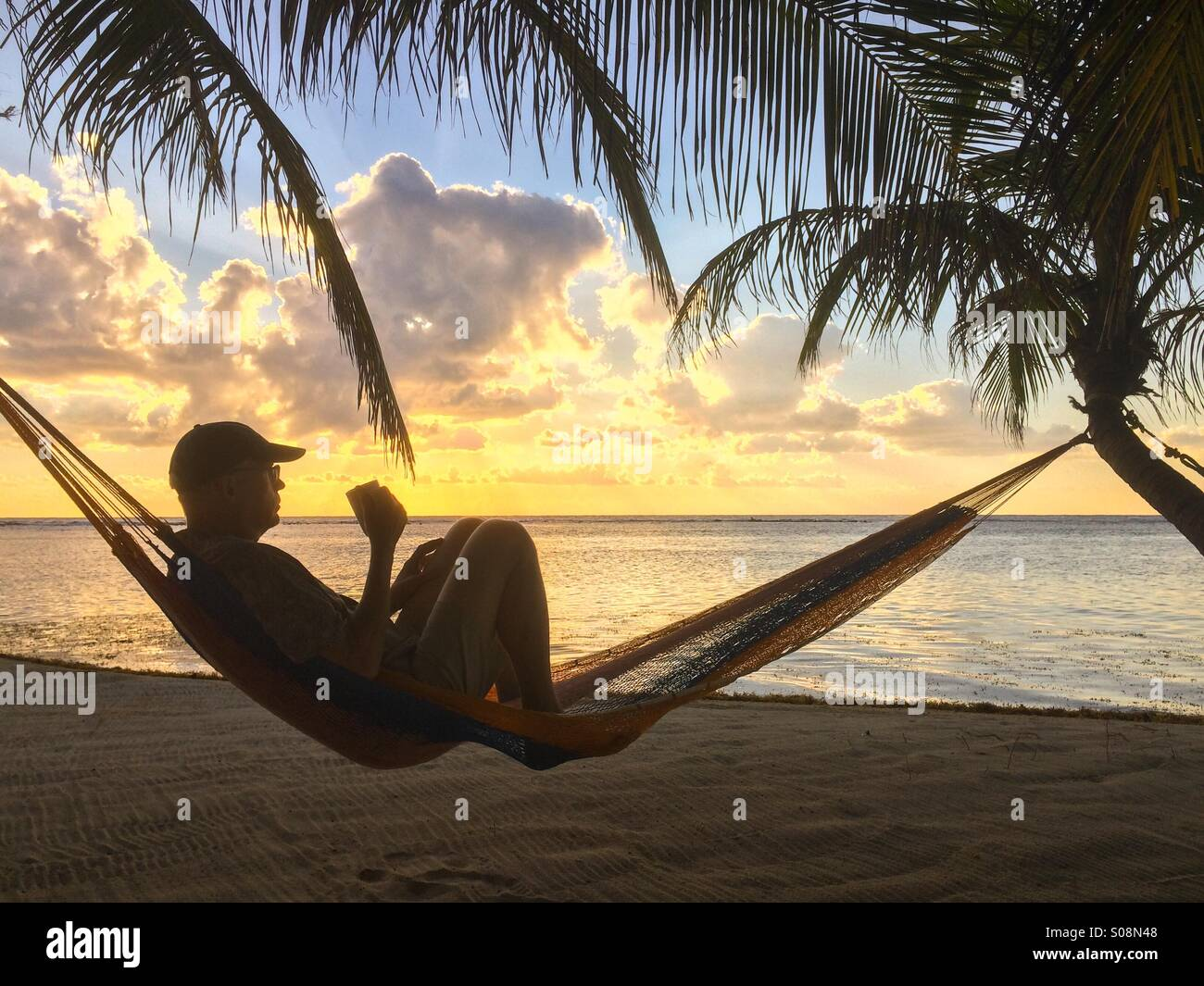 Man drinking coffee at the beach in hammock, Caribbean Sea, Belize - Stock Image