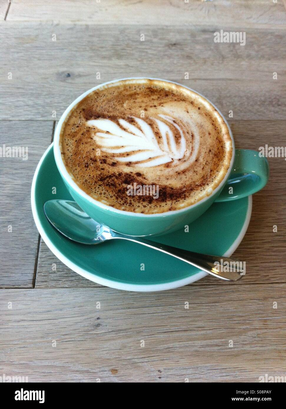 A cup of latte with art on top of it - Stock Image
