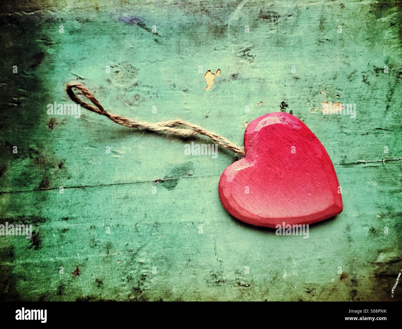 Red wooden heart with a thread on grungy background - Stock Image