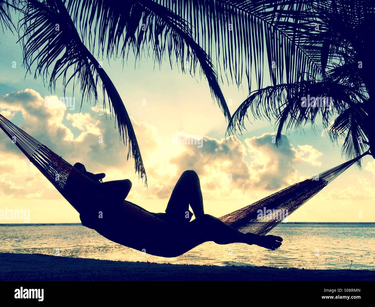 Man in Hammock ,South Water Caye, Belize - Stock Image