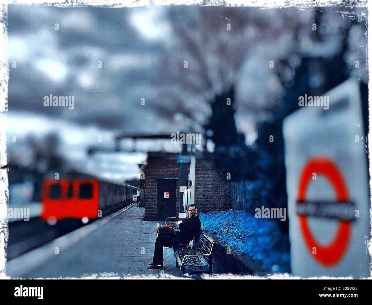 Man waiting for train at Ealing Common tube station, West London, UK Stock Photo