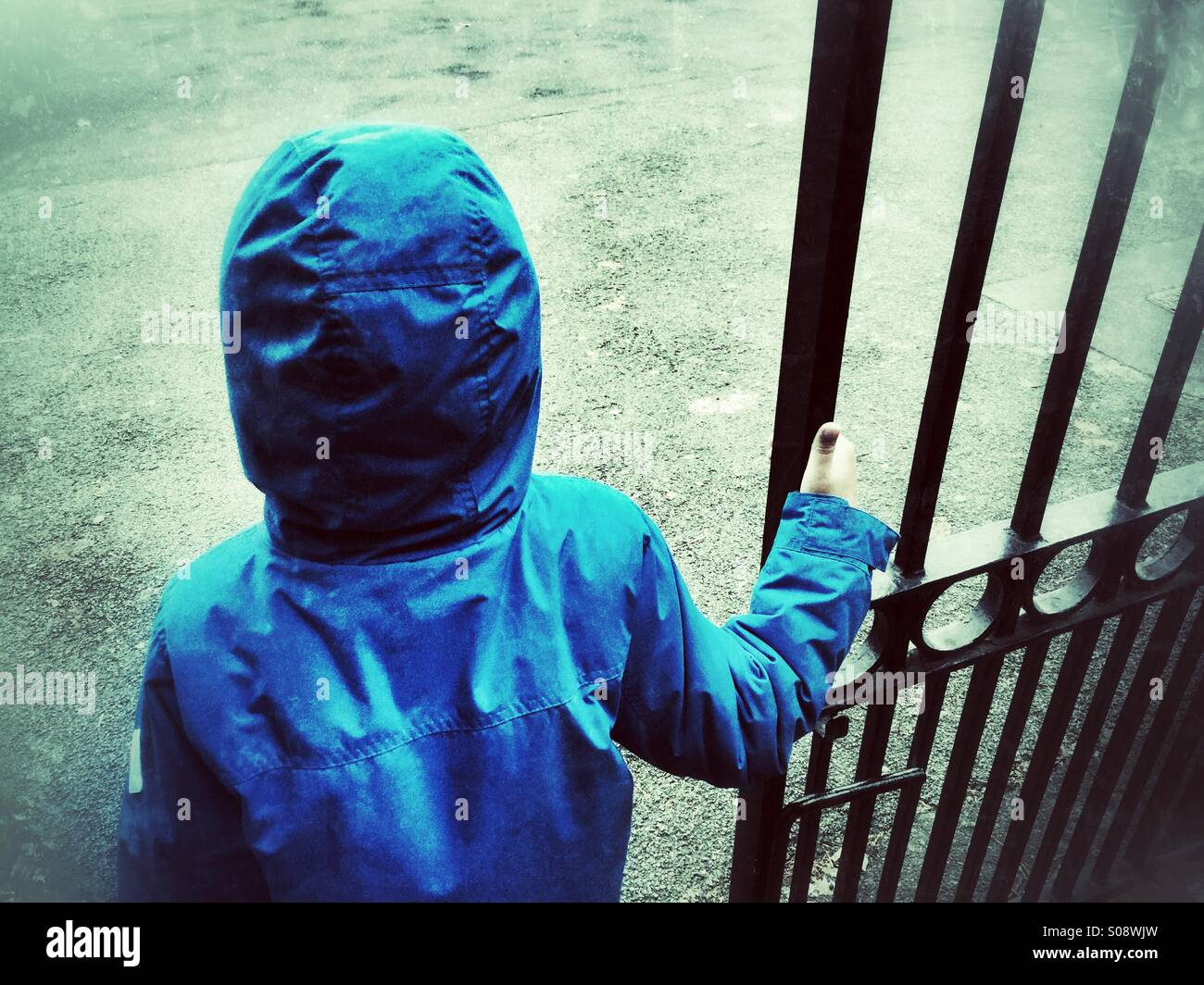 Little boy in blue coat waiting by the gate - Stock Image