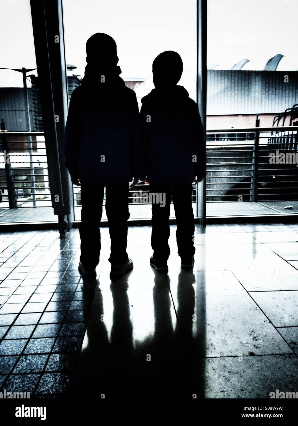 Two boys standing inside a building - Stock Image