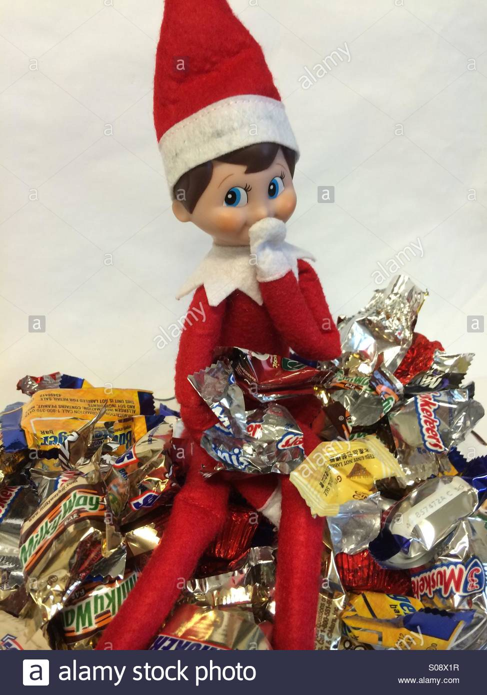A naughty Christmas elf eats candy in a dish - Stock Image