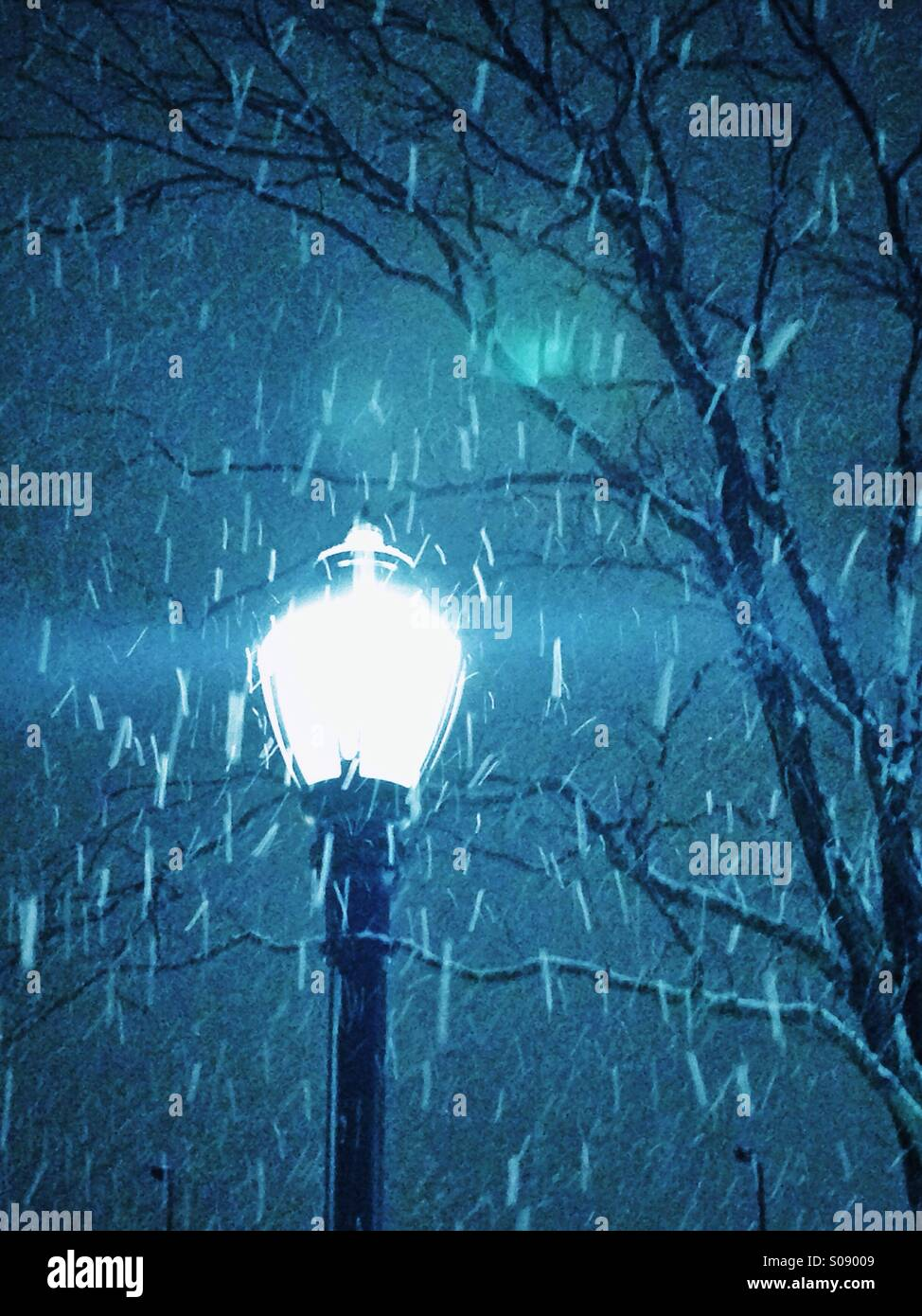 Snowfall in lamplight. - Stock Image