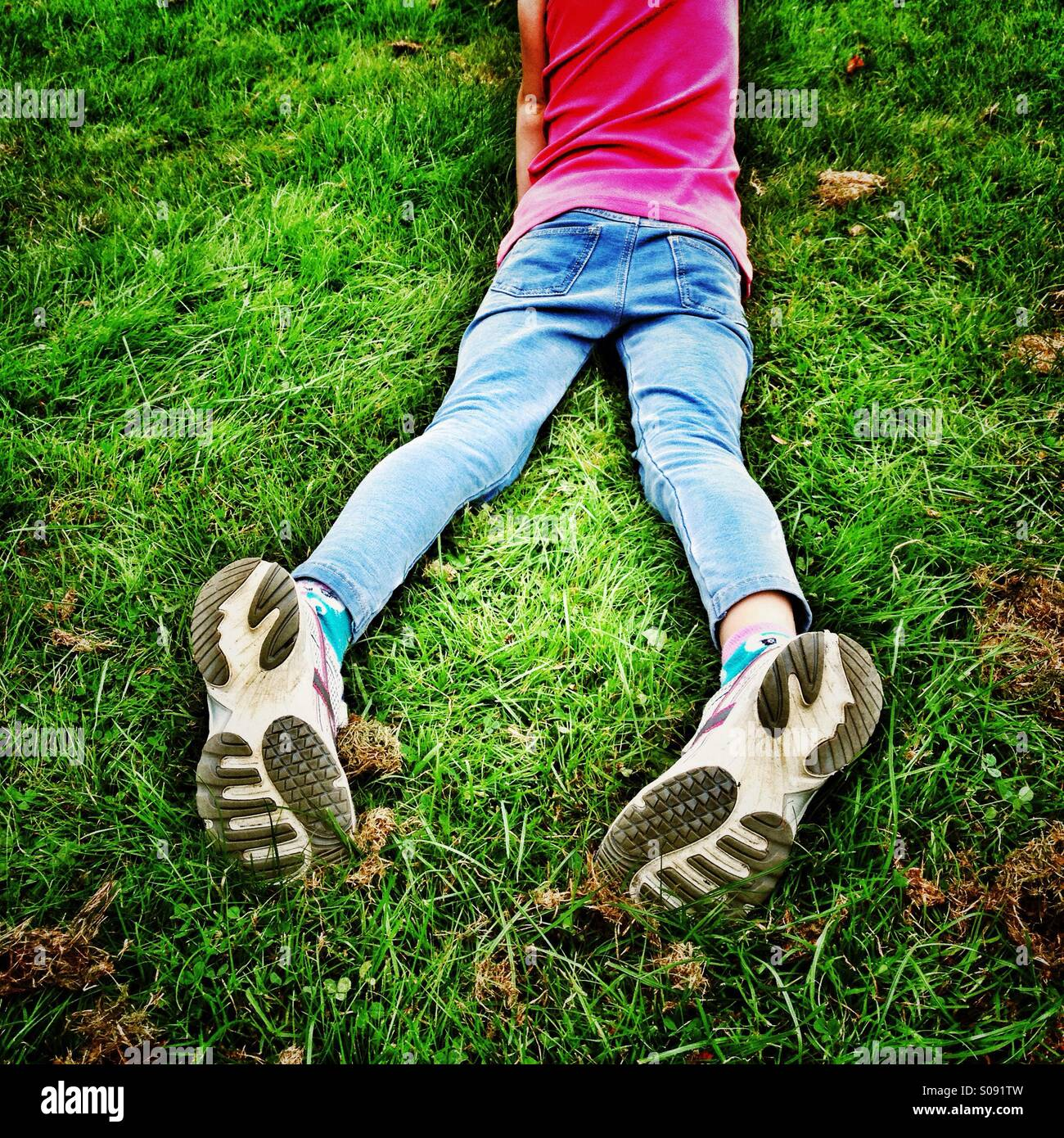 Legs of young girl lying in grass with soles of trainers facing upwards - Stock Image