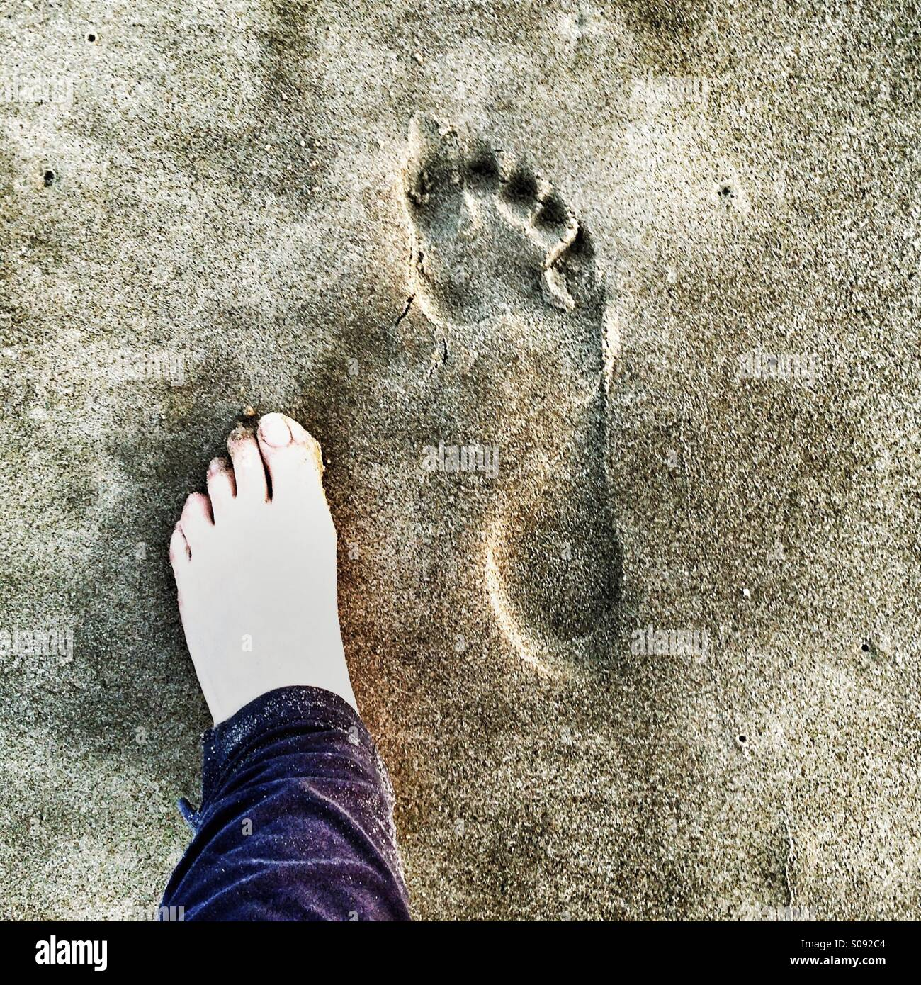 Left Barefoot, Right Footprint On The Sand - Stock Image