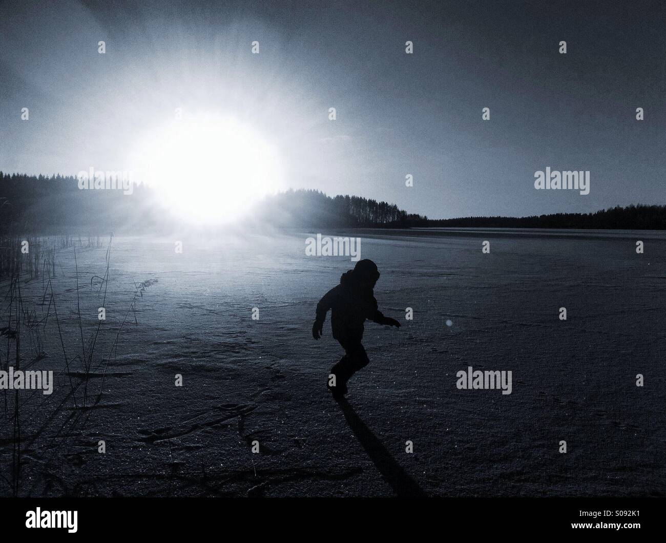 A boy running on ice during sunset - Stock Image