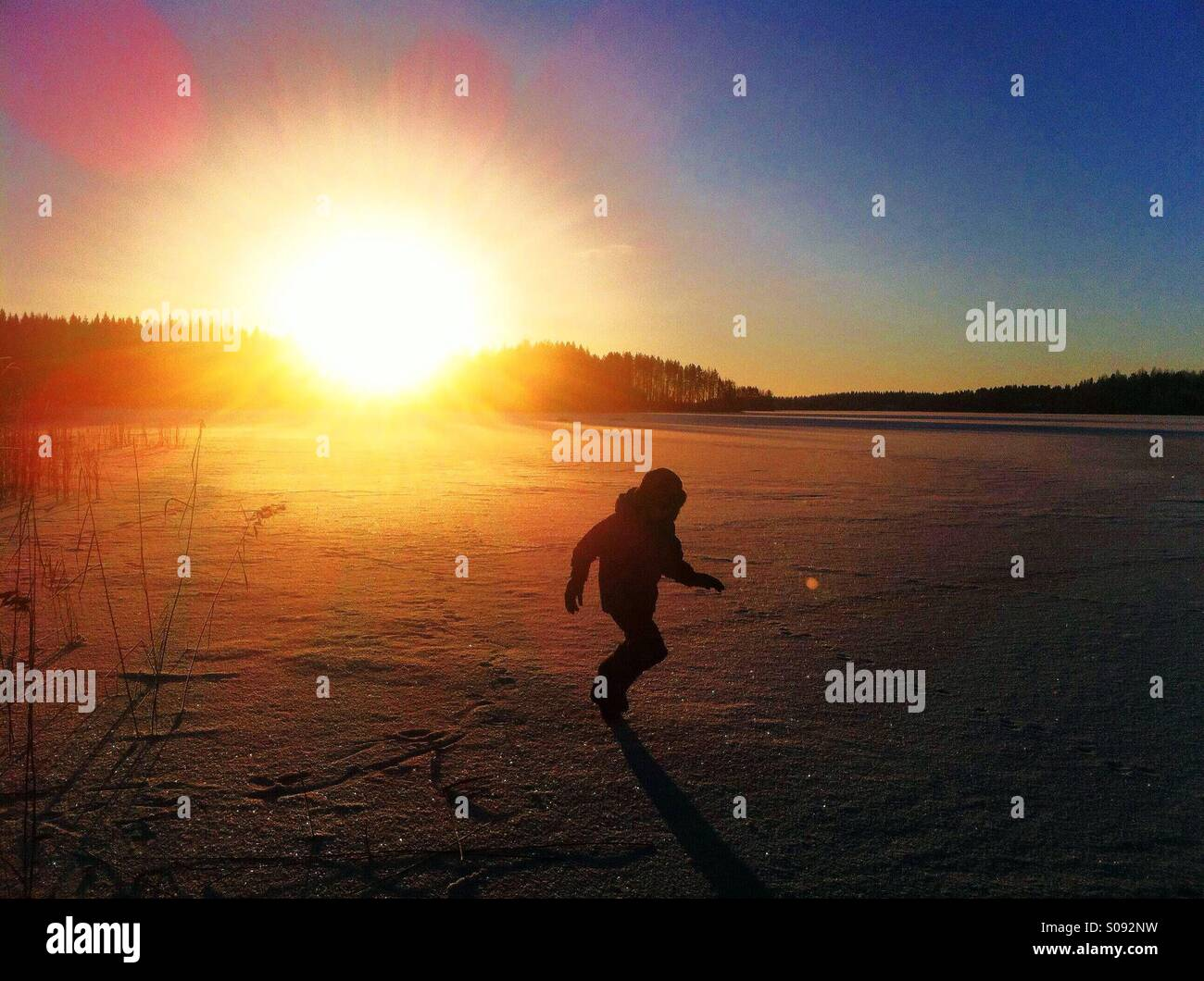 A boy running on ice of frozen lake in Kihniö, Finland Stock Photo