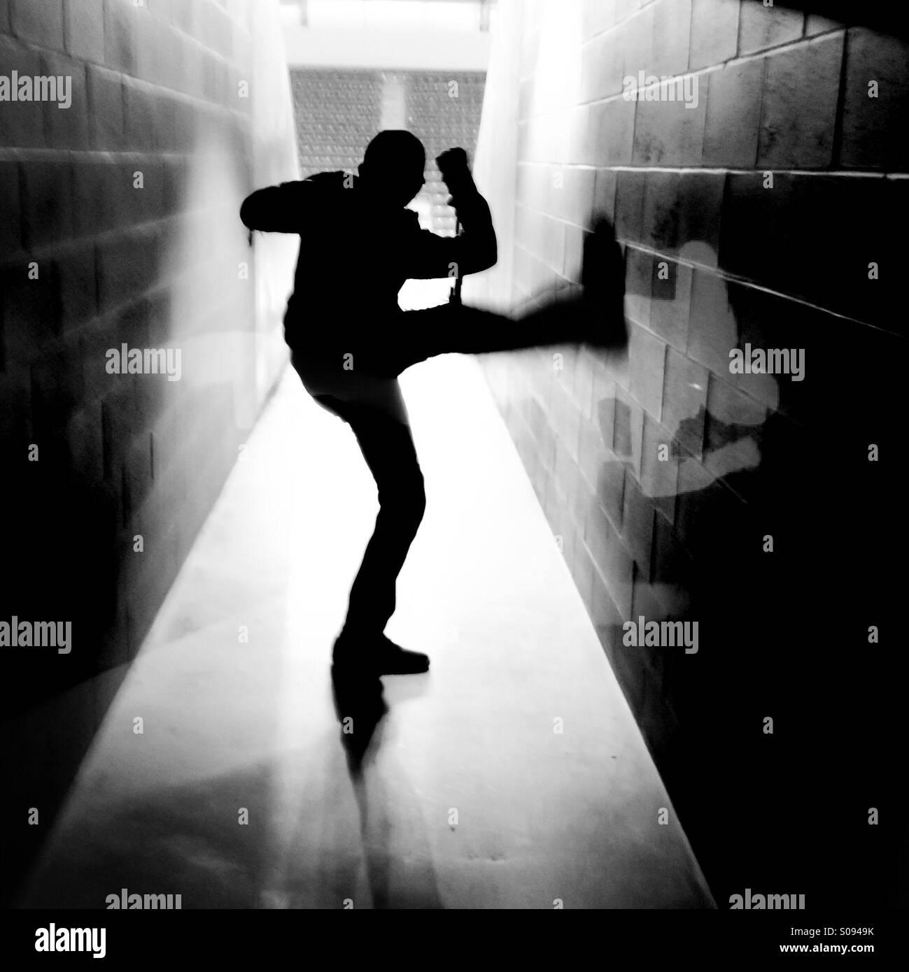 Silhouette of teen boy kicking - Stock Image