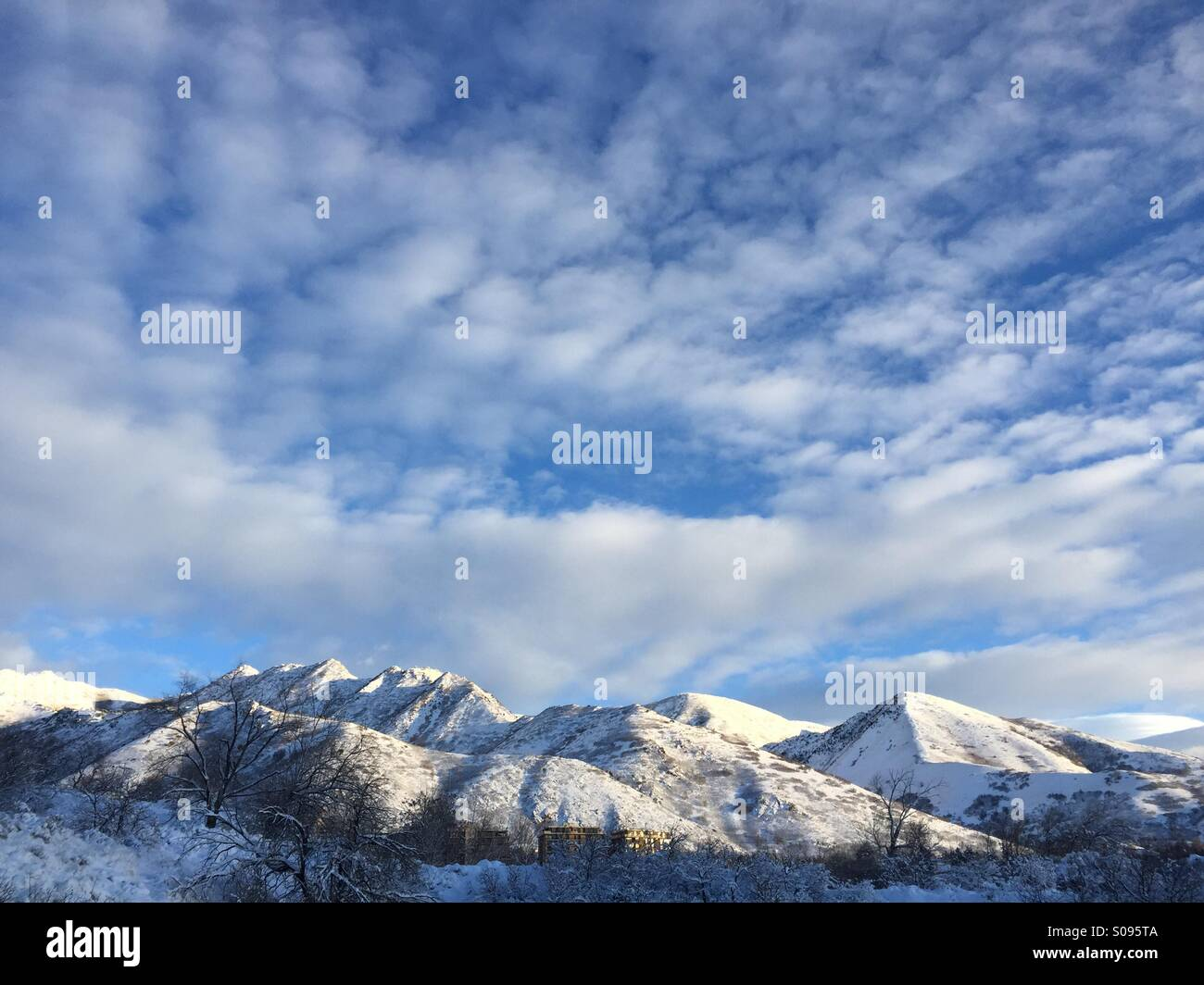 Whispy clouds float over the snow-covered Wasatch Front in Salt Lake City, UT. - Stock Image
