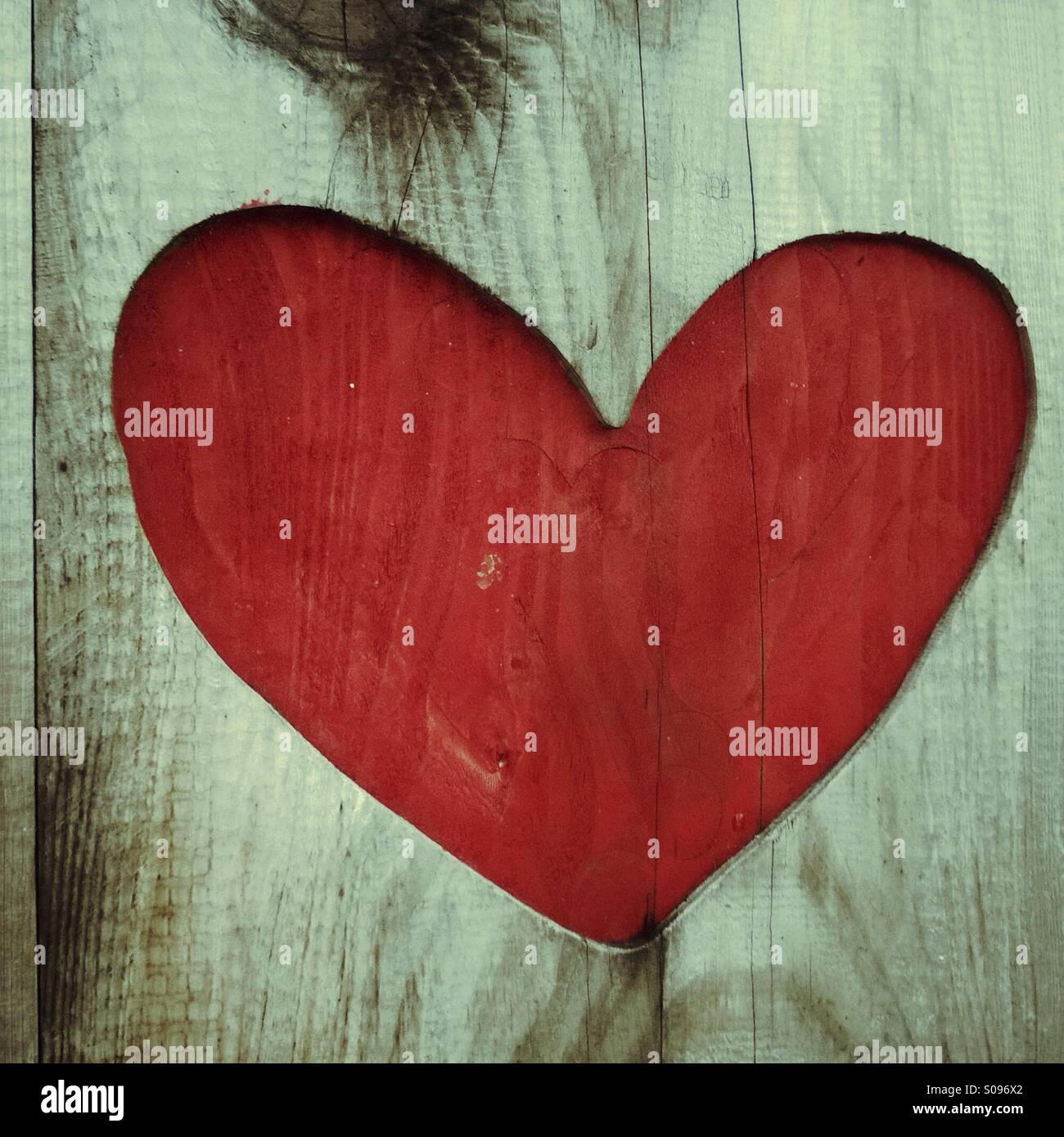 Red love heart shape in rustic wood - Stock Image