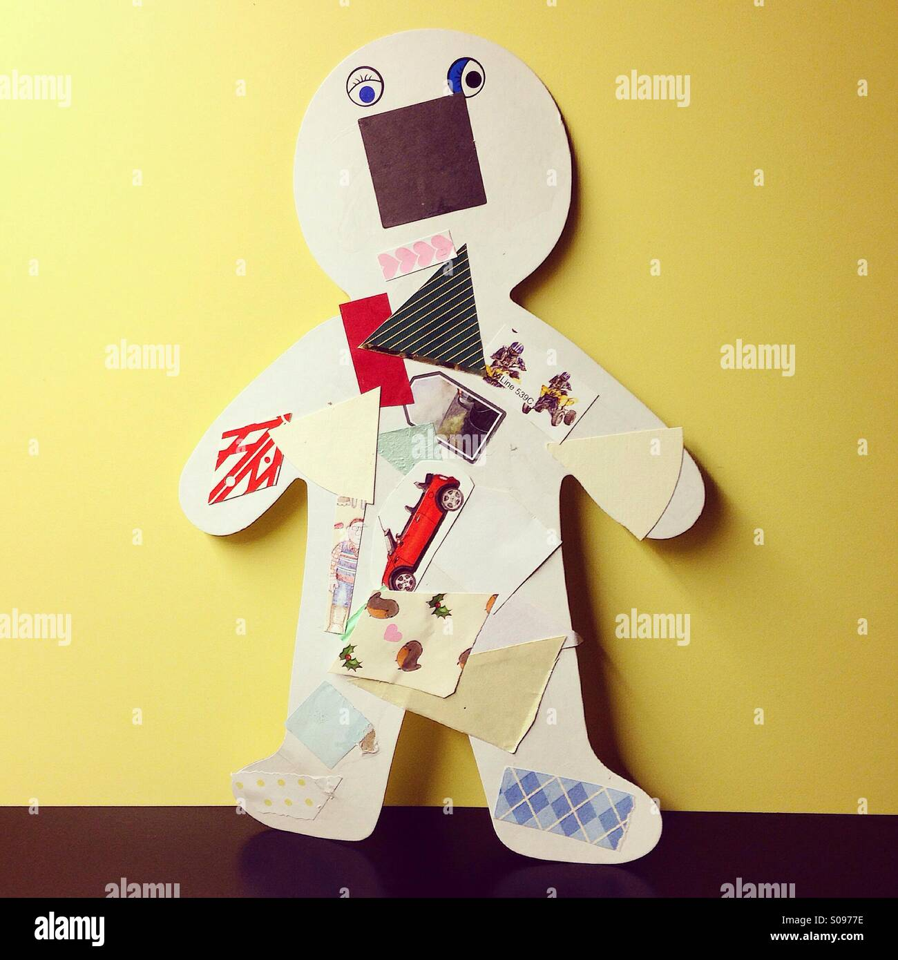 Child's nieve collage using cut out paper and shapes. - Stock Image