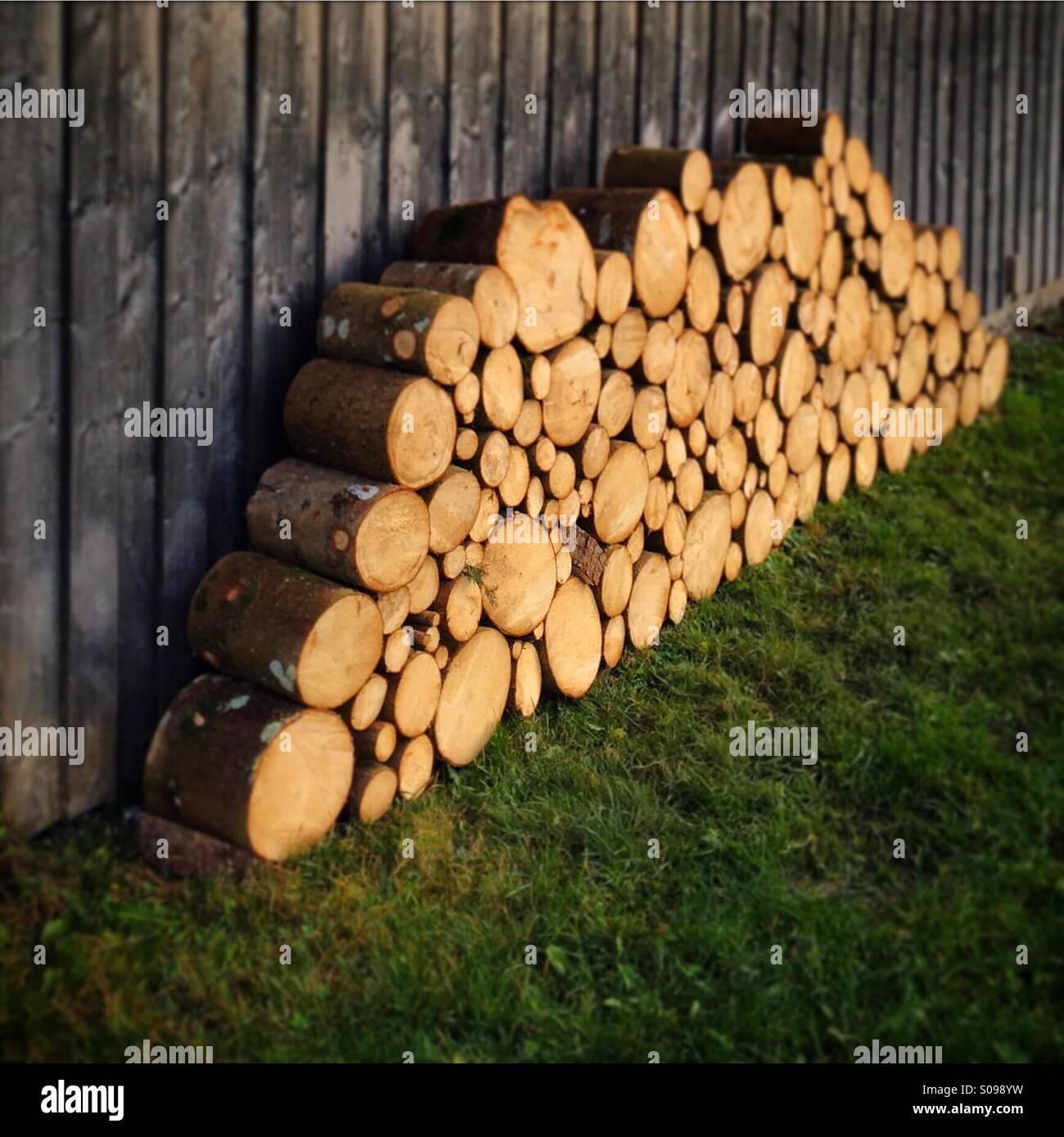Firewood logs stacked against a wooden building in Baveria, Germany. - Stock Image