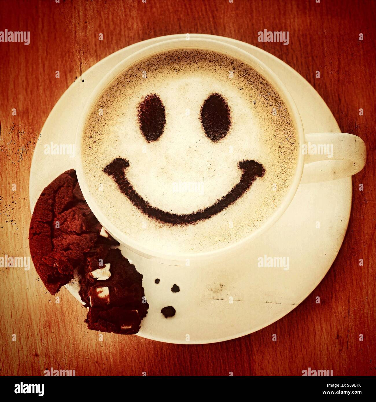 Coffee break - a cappuccino with a smiley face and a cookie biscuit - Stock Image