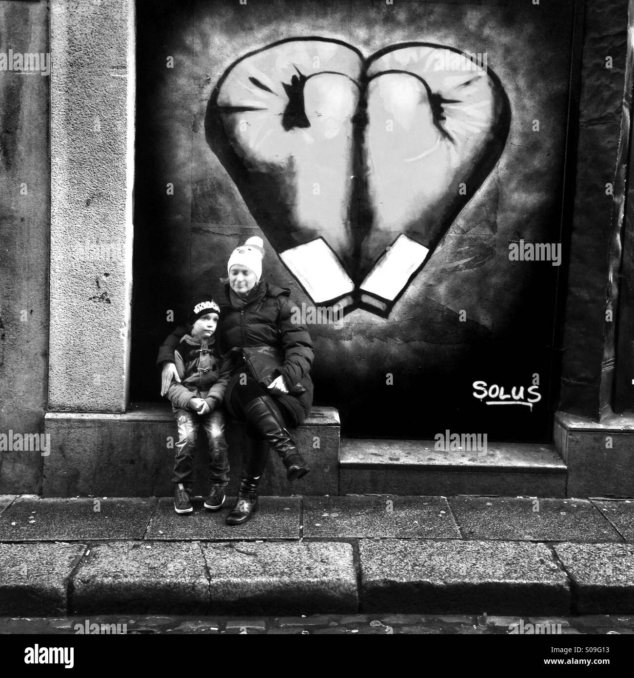 Mum & boy sit in front of graffiti in Dublin - Stock Image