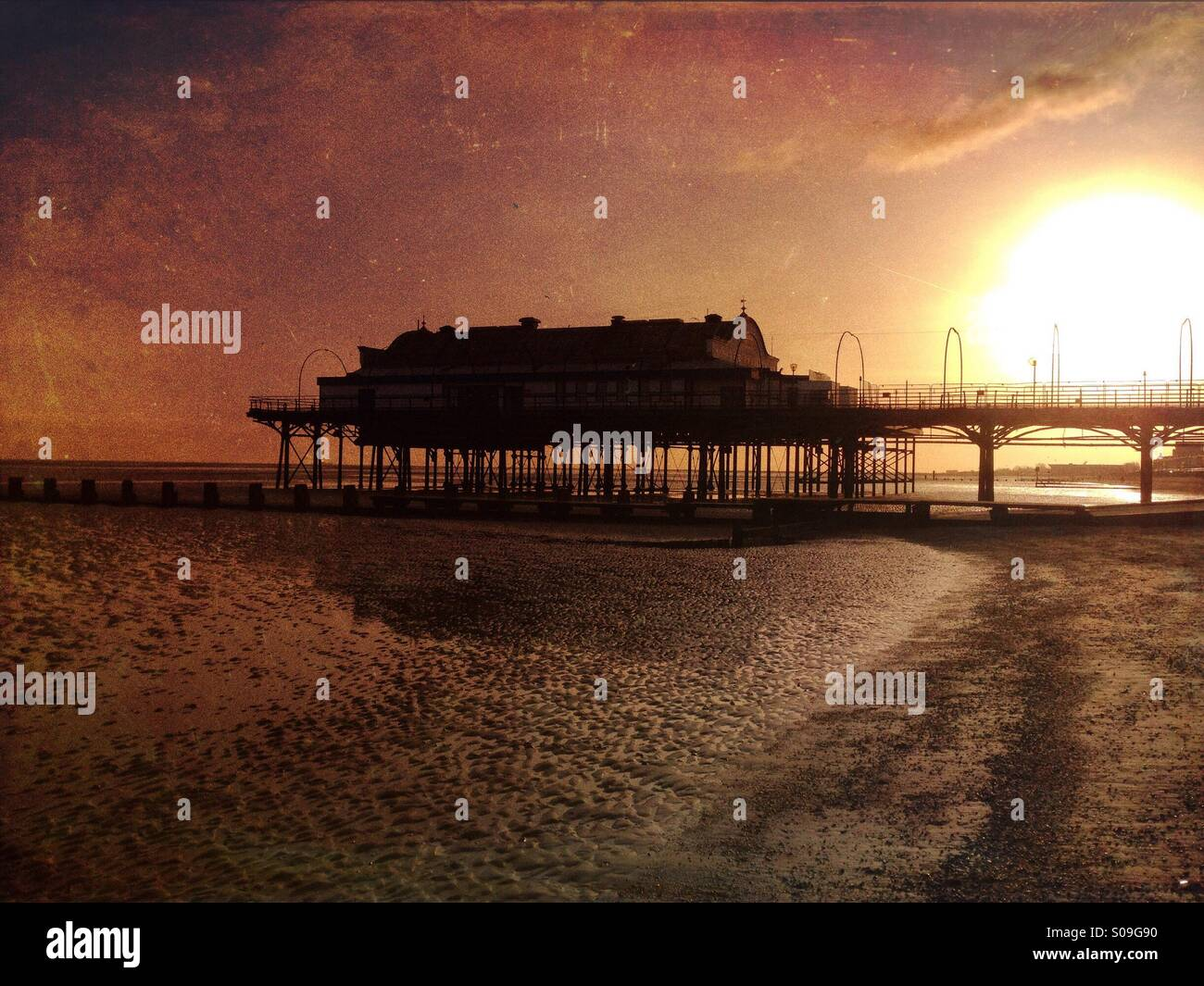 Atmospheric silhouette of Cleethorpes Pier at sunrise, architectural minimalism set against the rising sun, seen Stock Photo