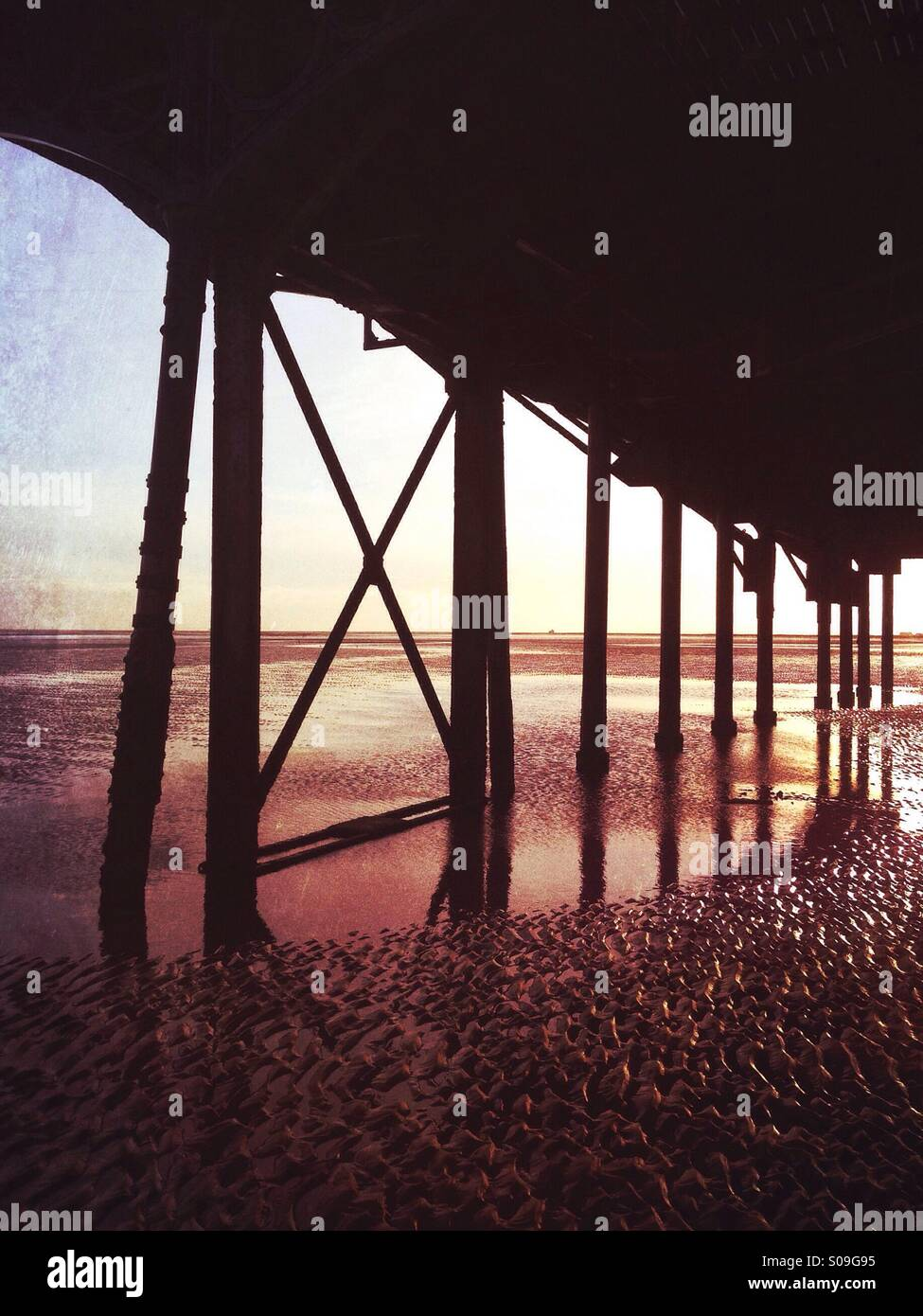 Rusting iron supporting a traditional seaside pier. - Stock Image