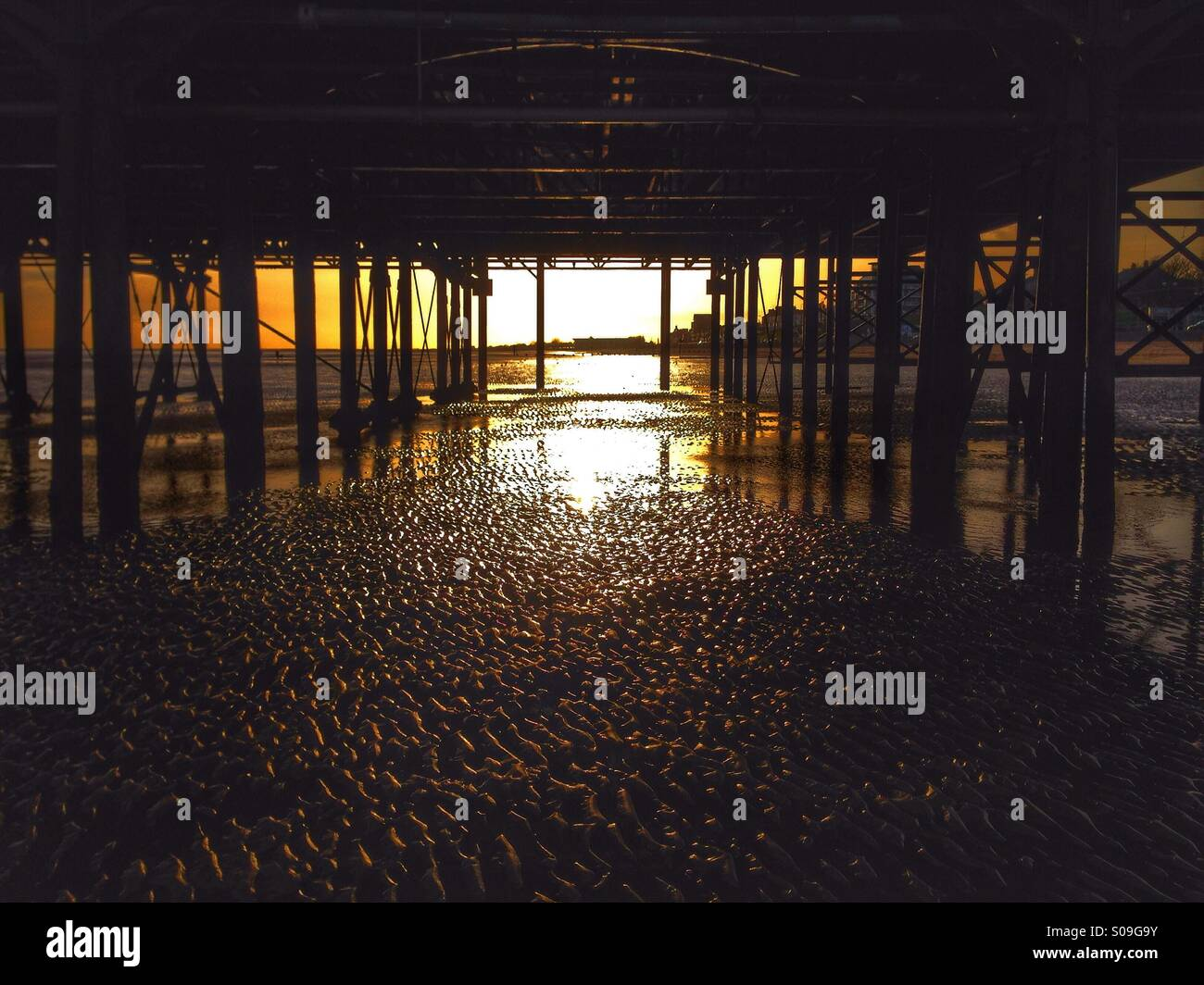 Underneath a seaside pier at sunrise. - Stock Image