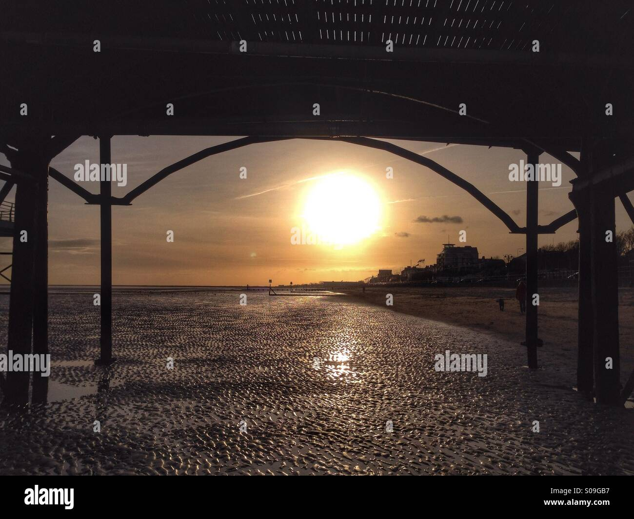 Sunrise seen from underneath a pier. - Stock Image