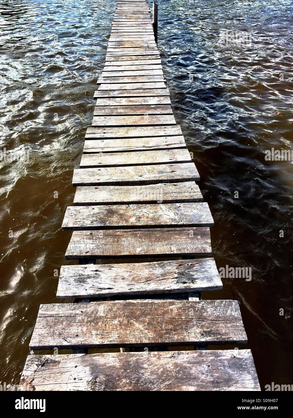 Rickety dock across water. - Stock Image