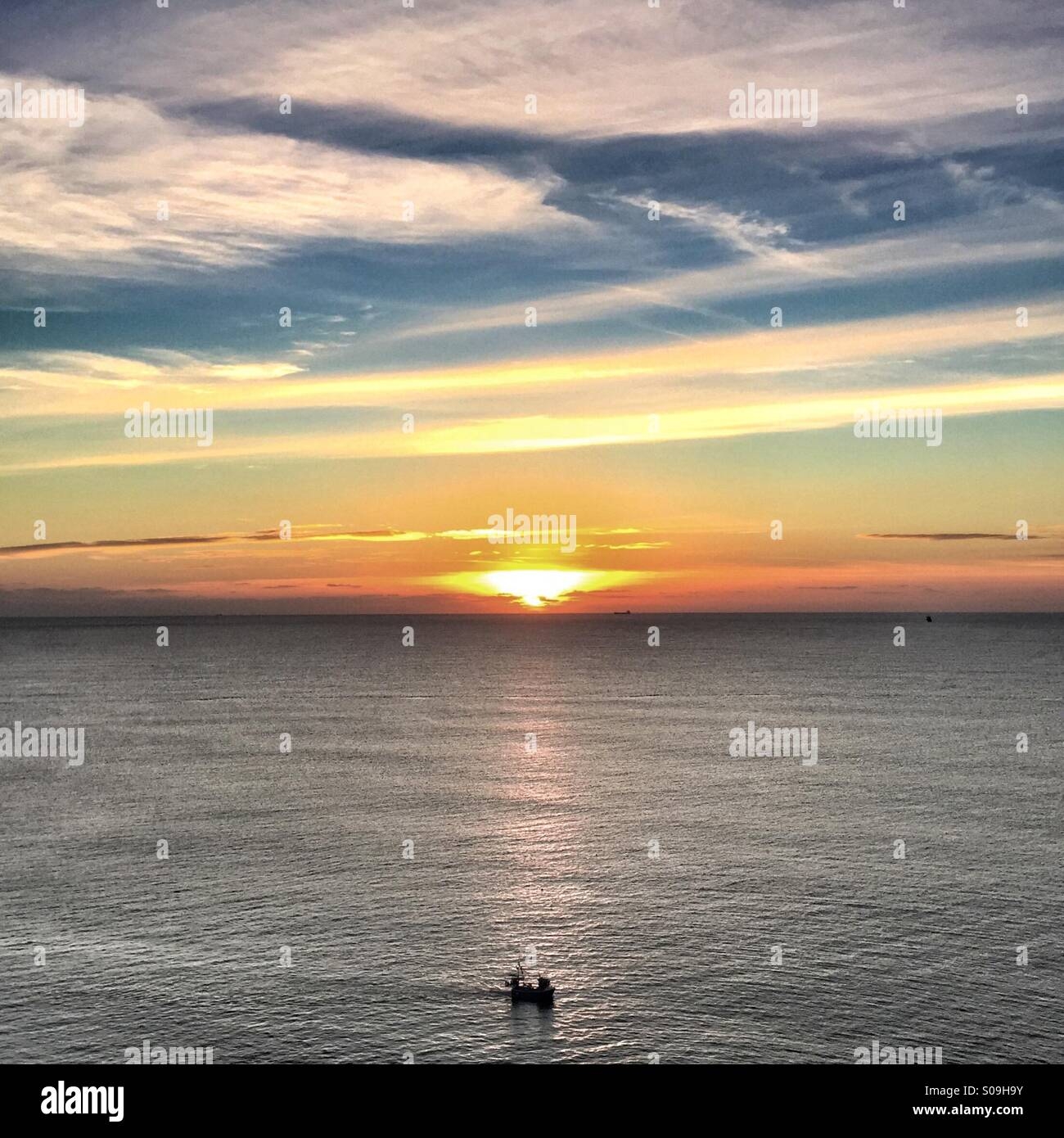 Sunset with lonely fishing boat off coast of Cornwall Stock Photo