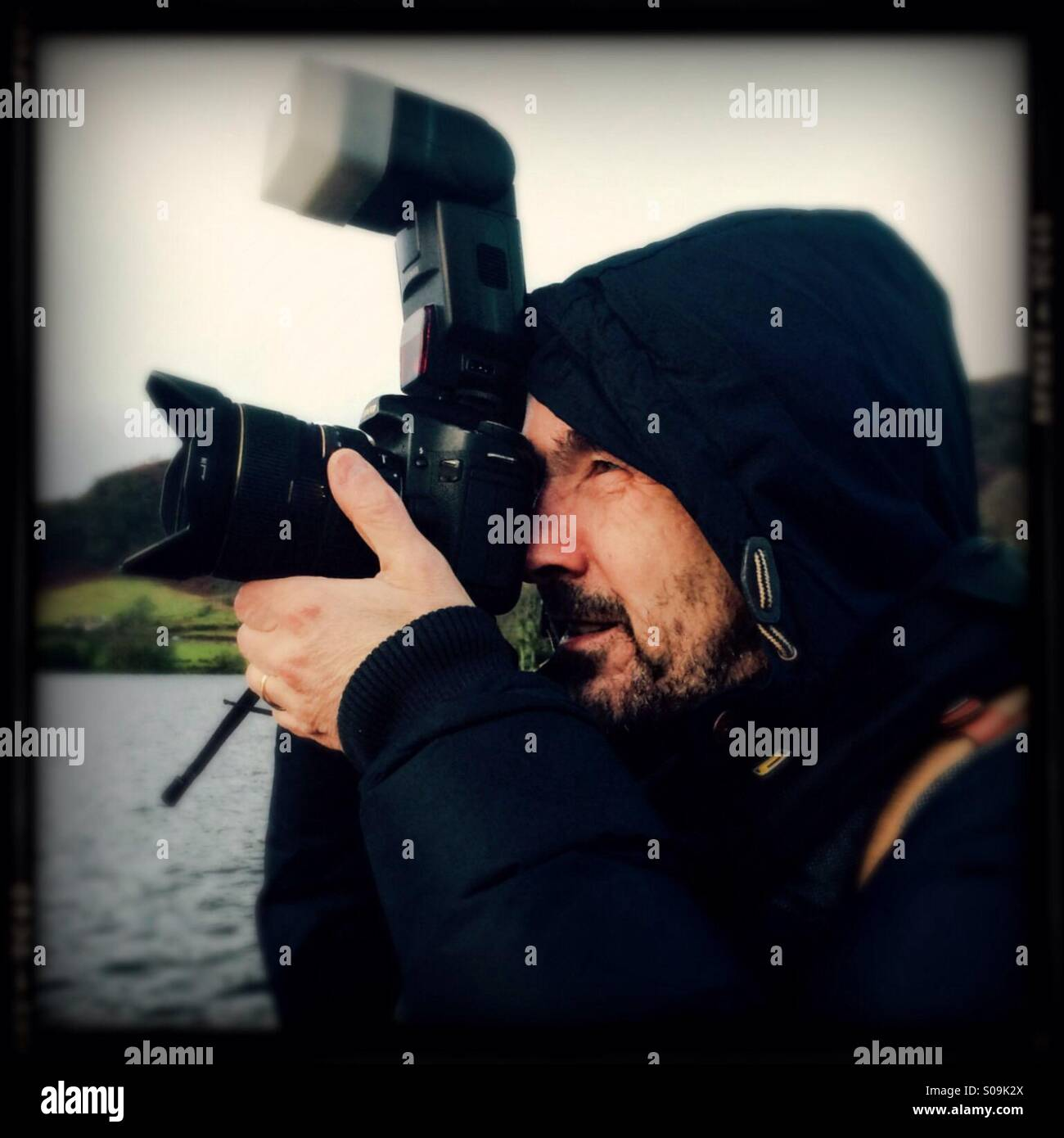 Photographer in outdoor gear composing shot on DSLR - Stock Image