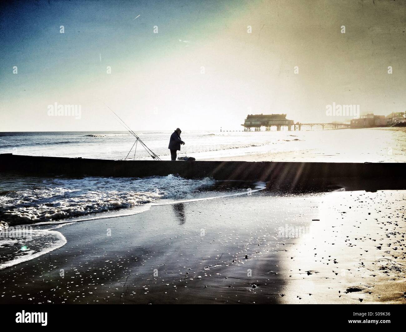 Sea fishing in winter surf on the shoreline of Cleethorpes beach with pier in background. Silhouette of fisherman - Stock Image