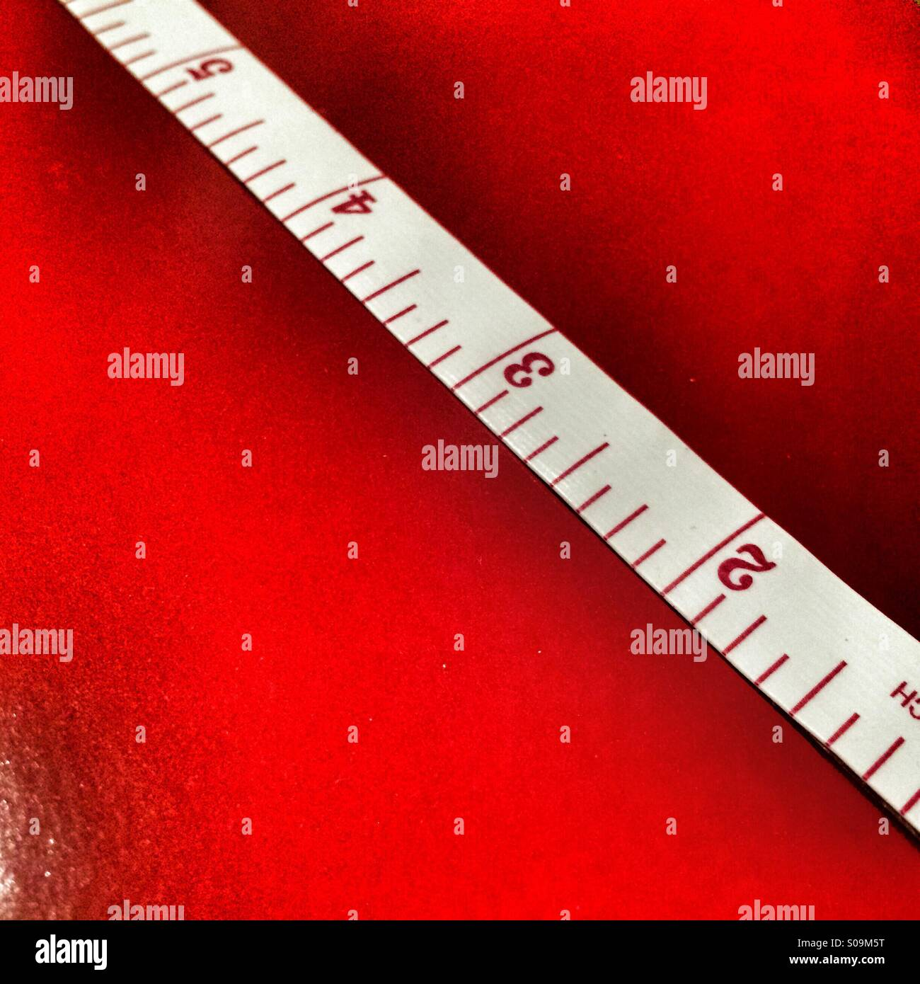 Tape measure showing inches on a red background - Stock Image