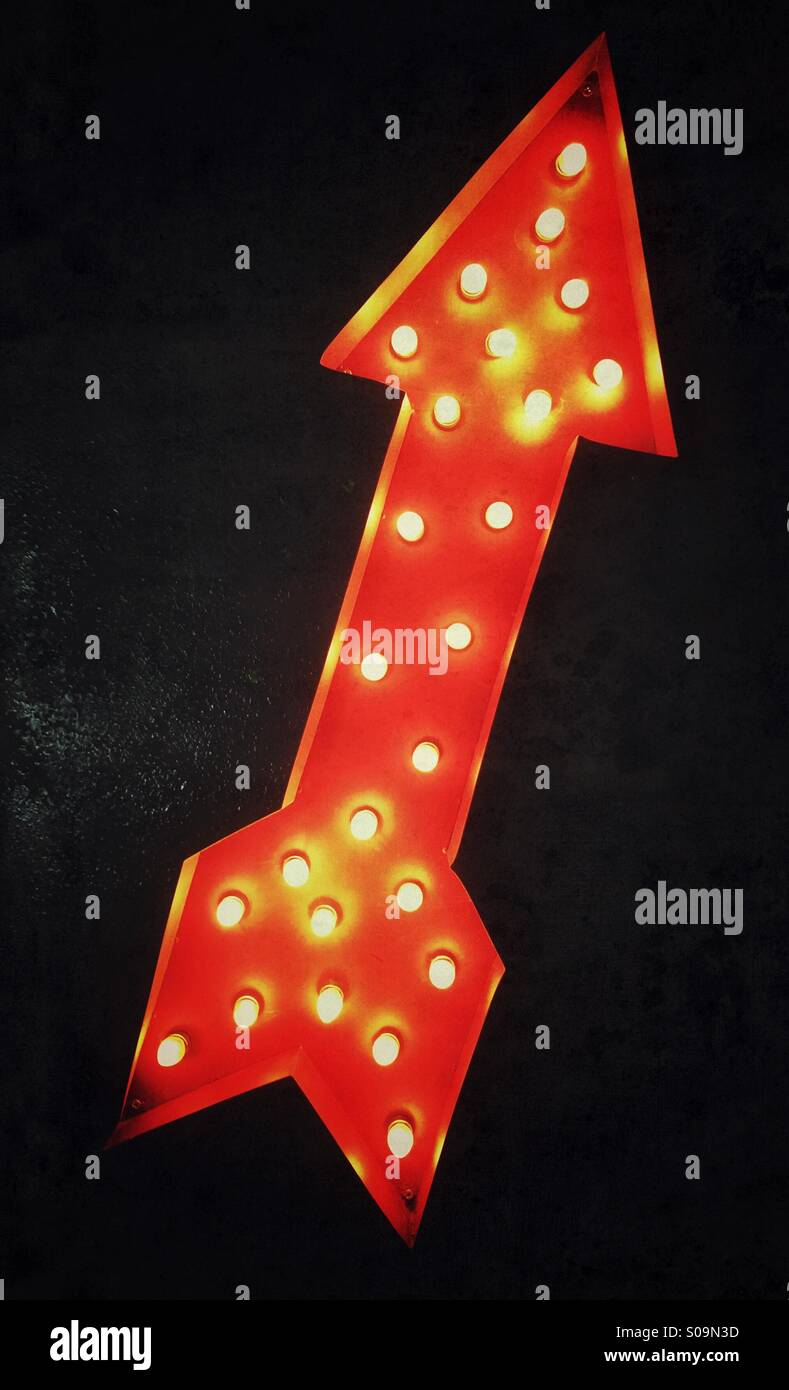 Illuminated arrow pointing up - Stock Image
