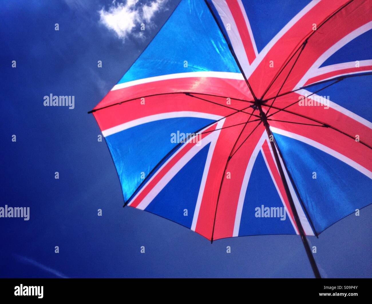 The sun shines through an umbrella with a design of the Union Flag of Great Britain, against a bright blue sky on - Stock Image