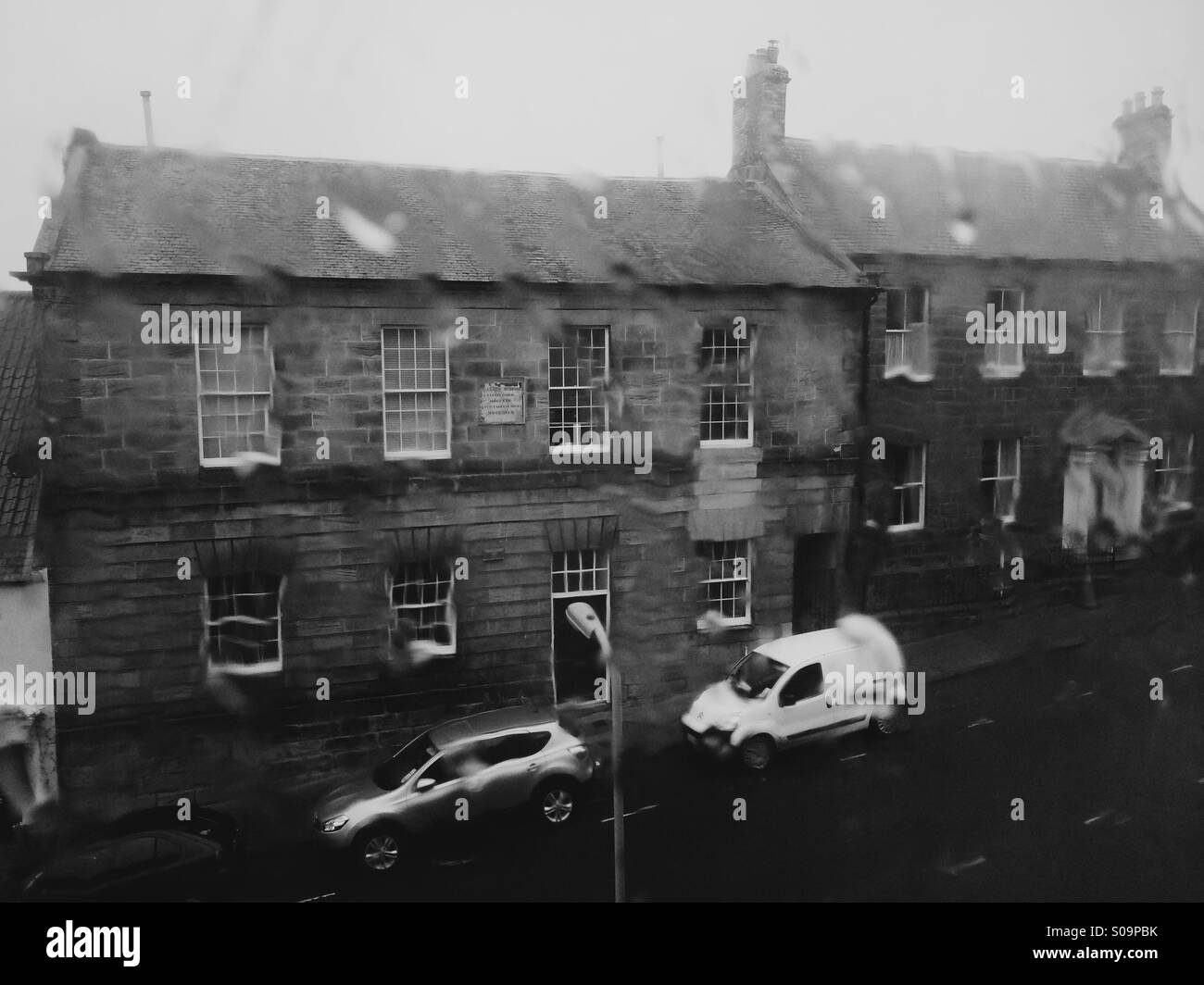 Miserable British weather - heavy rain on a window overlooking a residential street in Northumberland, UK. - Stock Image