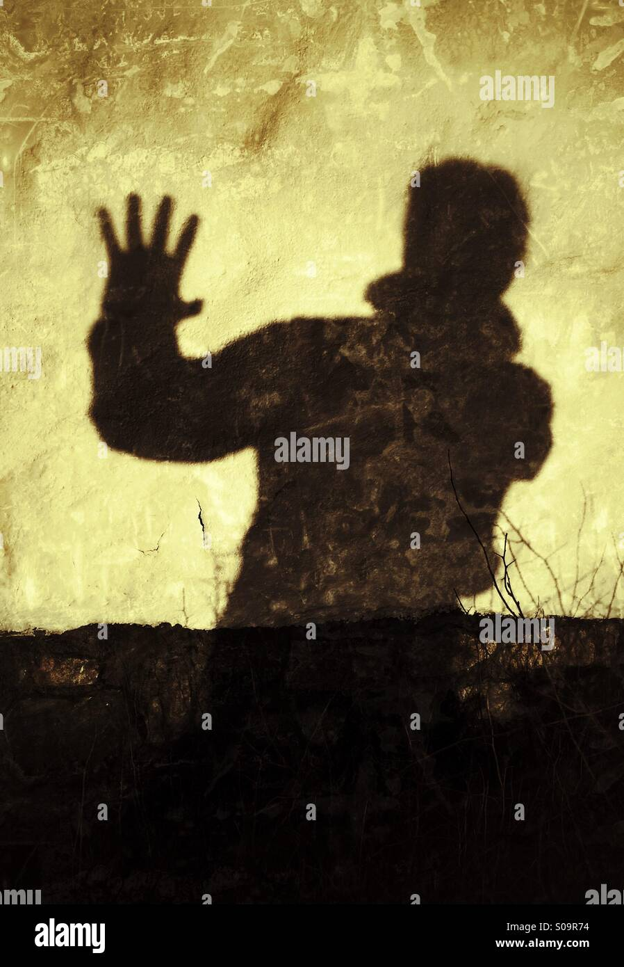 Stop! No more! Man casting a shadow on a wall expressing, Stop!, No more! Stock Photo