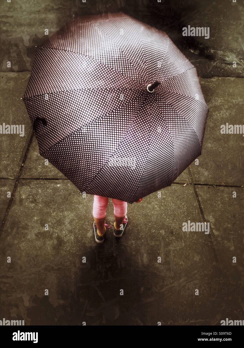 Little girl under an umbrella on a rainy day. - Stock Image
