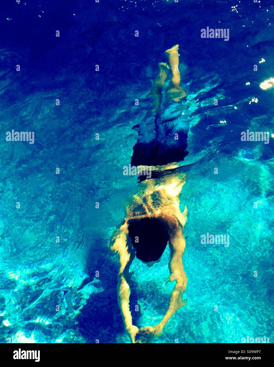Young man swimming underwater in swimming pool as the sun glistens through the water. - Stock Image