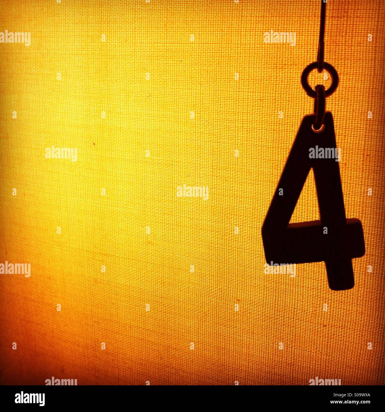 Silhouette of a number four hanging in front of an illuminated textured background - Stock Image