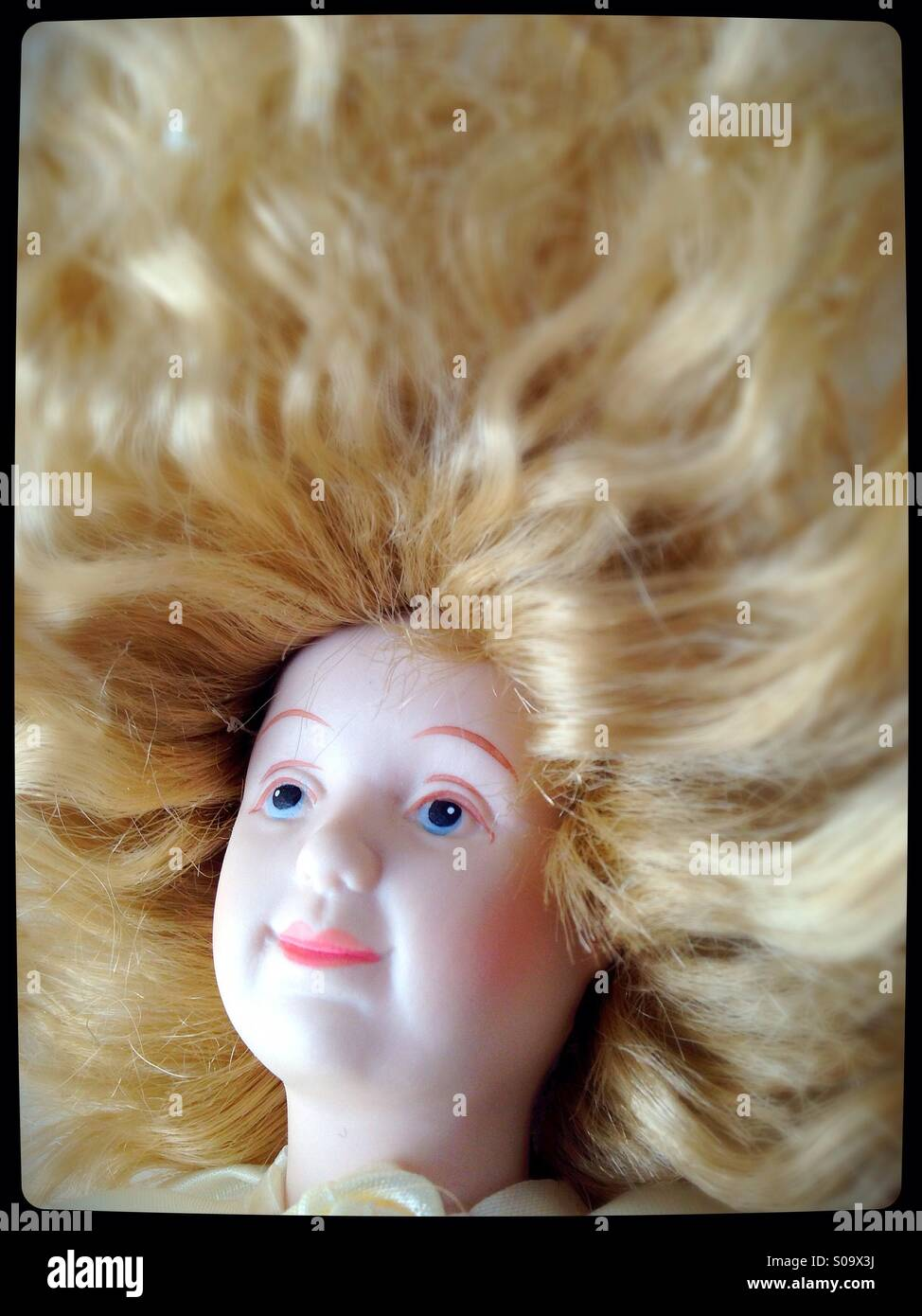 A doll with thick blond hair. - Stock Image