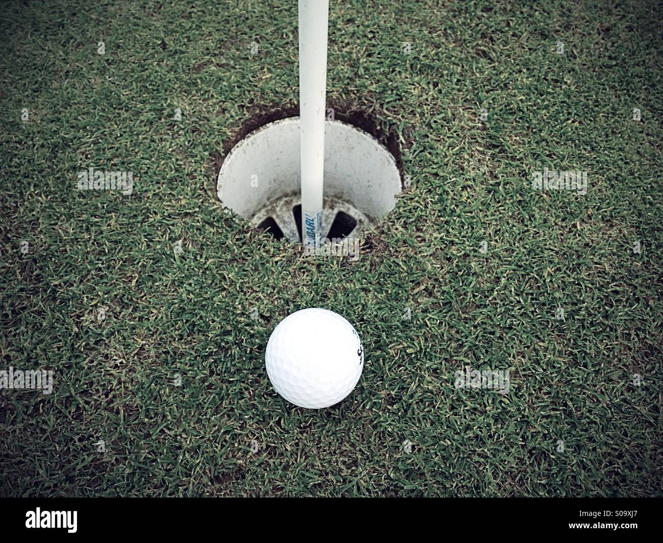 Golf ball near to hole - Stock Image