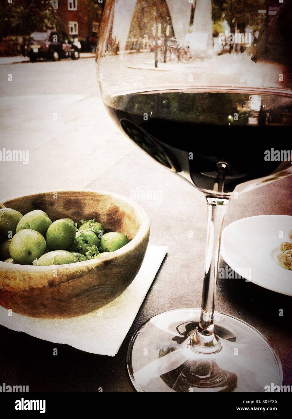 Having a glass of wine with fresh olives at Notting Hill, London - Stock Image
