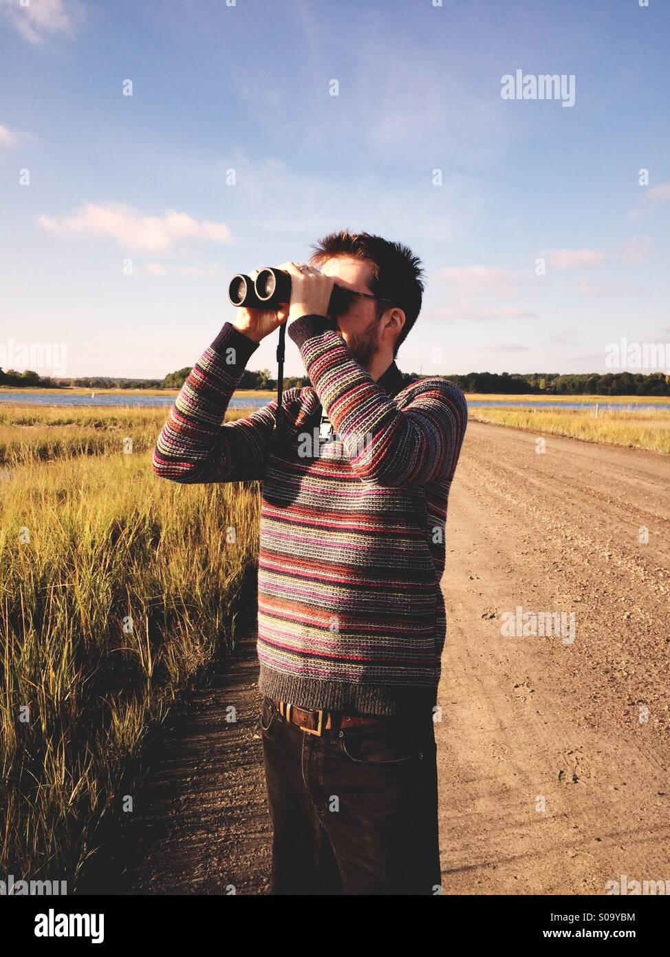 A man birdwatching by a salt marsh in Connecticut, USA. - Stock Image