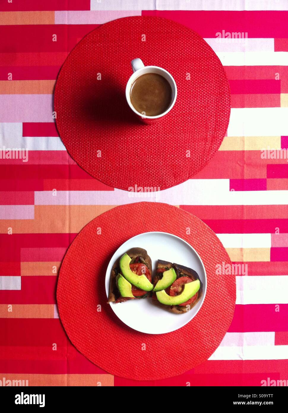 Vegan breakfast on red geometrical tablecloth with coffee and open sandwiches - Stock Image