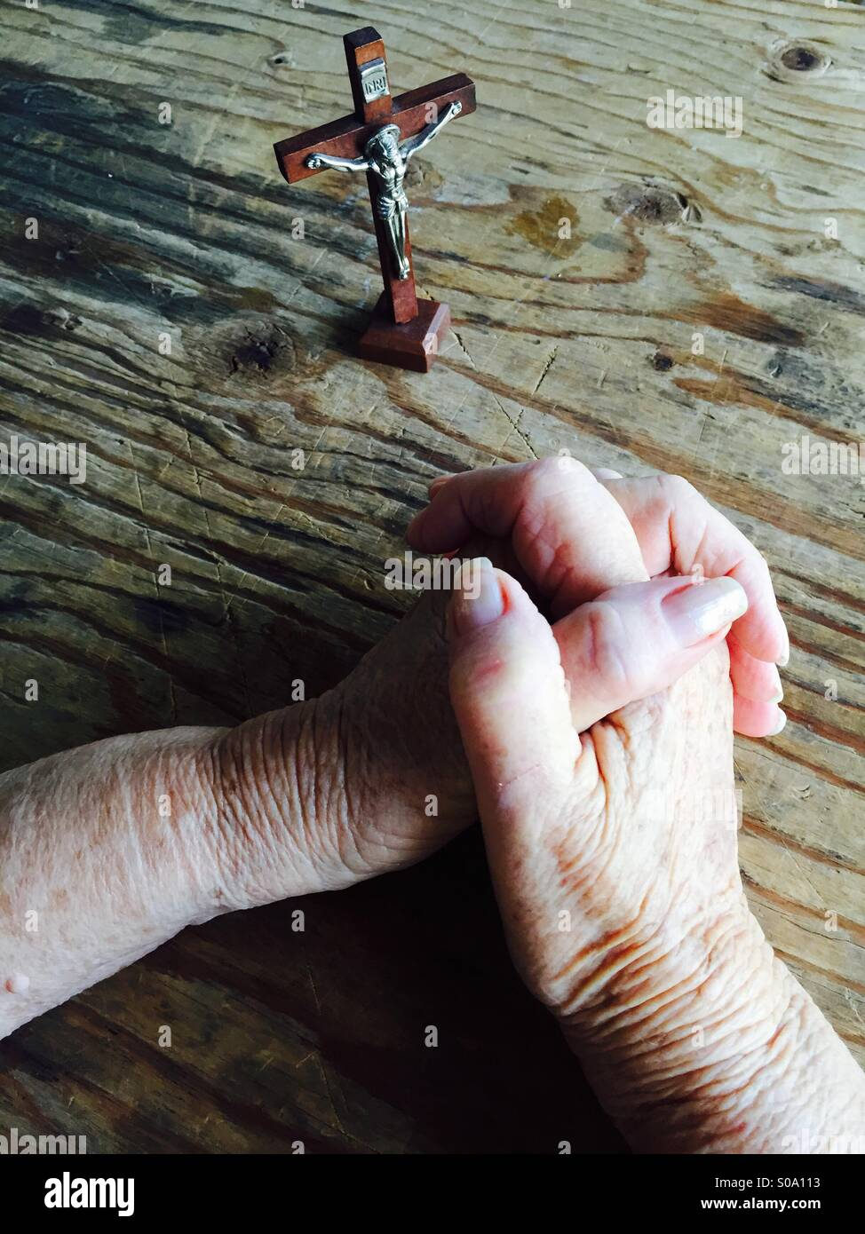 Folded hands in prayer and a crucifix of Christ. - Stock Image
