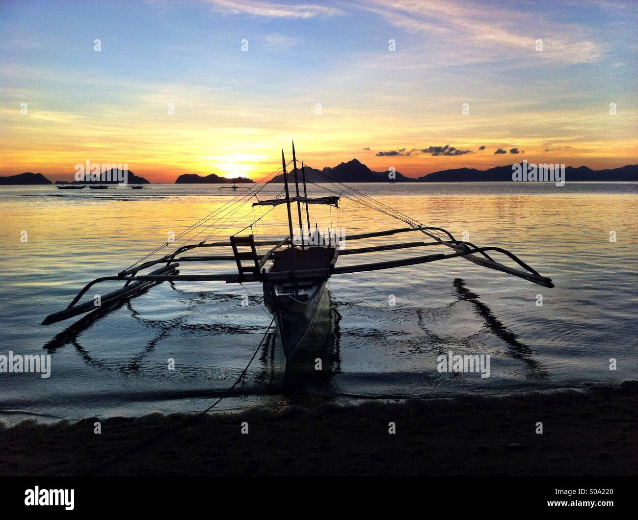 Silhouette of traditional Philippine fishing bangka boat in El Nido on Palawan island with Thousand islands at sunset - Stock Image